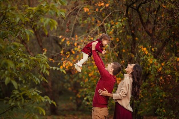 Glückliche familie mit kleiner tochter, die spaß auf einem spaziergang im park hat Premium Fotos