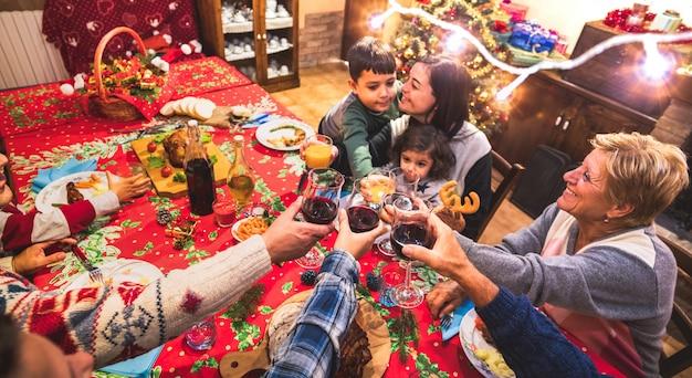 Glückliche familie mit mehreren generationen, die spaß an der weihnachtsabendessenparty hat Premium Fotos