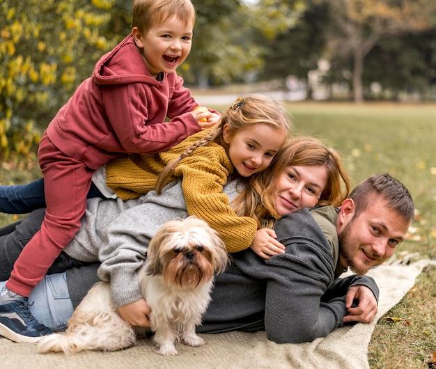 Glückliche familie mit niedlichem hund in der natur Premium Fotos