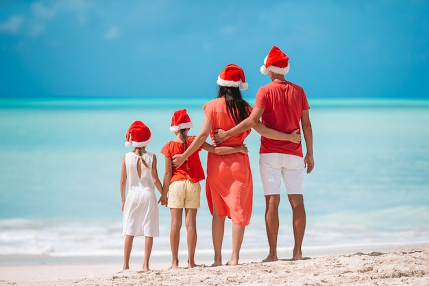 Glückliche familie mit zwei kindern in santa hat in den sommerferien Premium Fotos