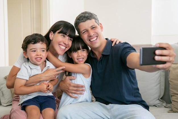 Glückliche familie mit zwei kleinen kindern, die zu hause zusammen auf der couch sitzen und selfie nehmen Kostenlose Fotos