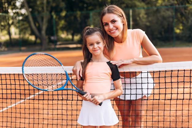 Glückliche familie posiert gut auf dem tennisplatz Premium Fotos