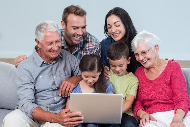Glückliche familie sitzt auf dem sofa Premium Fotos