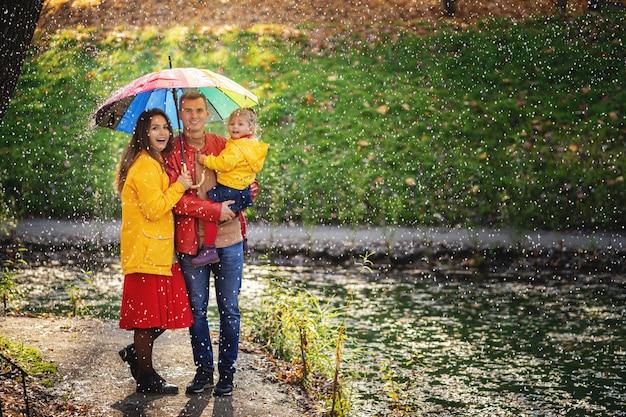 Glückliche familie unter dem regenschirm verstecken sich vor dem regen. Premium Fotos