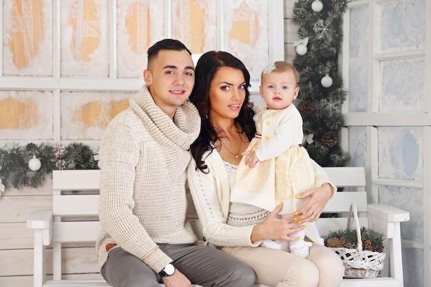 Glückliche familie, vater, mutter und tochter auf der veranda mit weihnachtsschmuck Premium Fotos