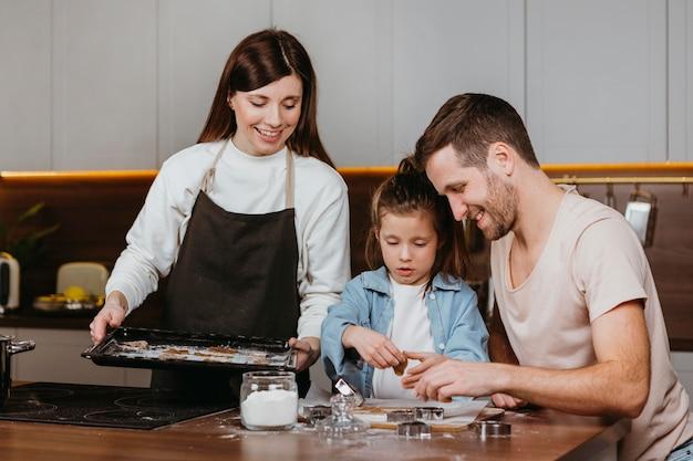 Glückliche familie von vater und mutter mit tochter, die zusammen kochen Kostenlose Fotos