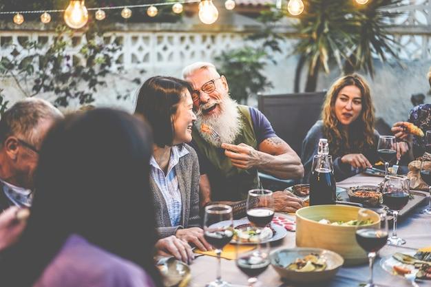 Glückliche familienleute, die spaß am grillabendessen haben - gemischtrassige freunde, die beim grillessen essen Premium Fotos