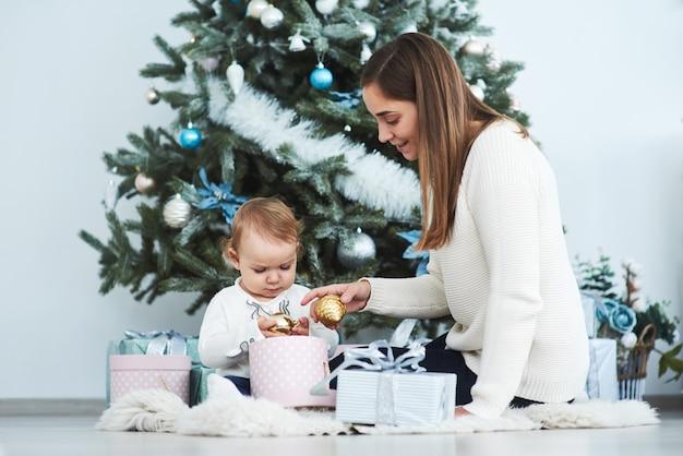Glückliche familienmutter und kindertochter am weihnachtsmorgen am weihnachtsbaum mit geschenken Premium Fotos