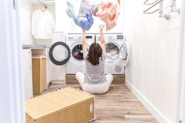 Glückliche familienmutterhausfrau in der waschküche mit der waschmaschine, die oben kleidung wirft Premium Fotos