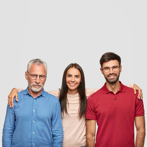 Glückliche familienpose für das gemeinsame foto: positiver älterer vater, erwachsene tochter und sohn umarmen sich, lächeln freundlich, posieren gegen weiße wand. konzept für menschen, generationen und beziehungen Kostenlose Fotos