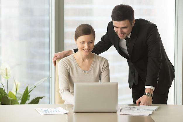 Glückliche firmenangestellte, die laptop im büro verwenden Kostenlose Fotos
