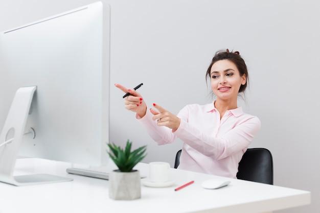 Glückliche frau am schreibtisch zeigend auf den computer Kostenlose Fotos