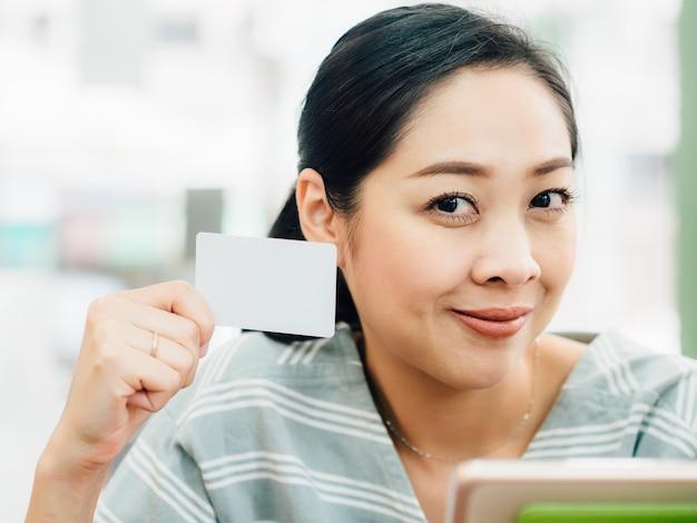 Glückliche frau benutzt eine weiße modellkreditkarte für das on-line-einkaufen auf tablette. Premium Fotos