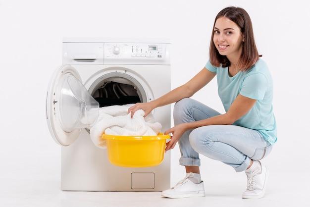 Glückliche frau der seitenansicht, die tücher von der waschmaschine nimmt Kostenlose Fotos