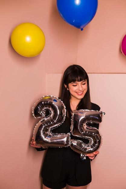 Glückliche frau, die 25 foliengeburtstagsballon hält Kostenlose Fotos