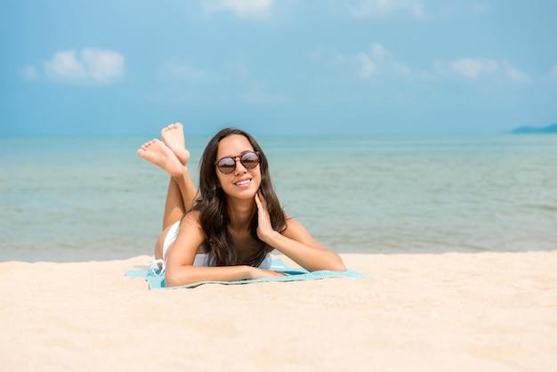 Glückliche frau, die am strand im sommer sich entspannt Premium Fotos