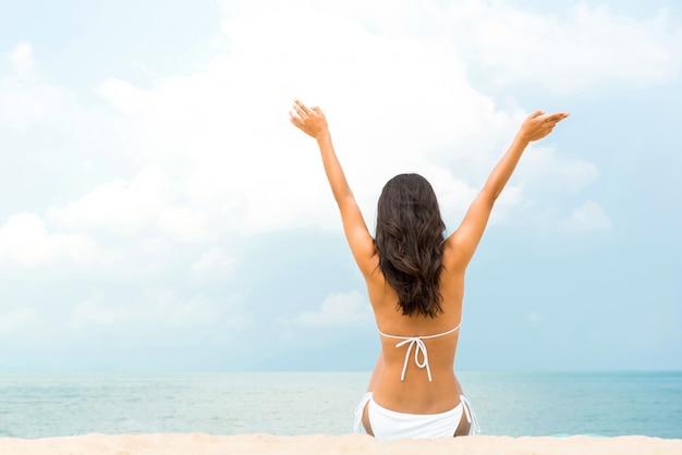Glückliche frau, die am strand im sommer sitzt Premium Fotos