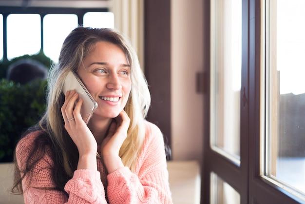 Glückliche frau, die am telefon lächelt und spricht Premium Fotos