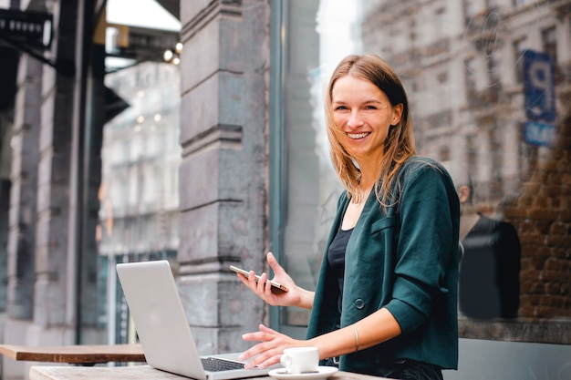 Glückliche frau, die an einem laptop im freien arbeitet Premium Fotos