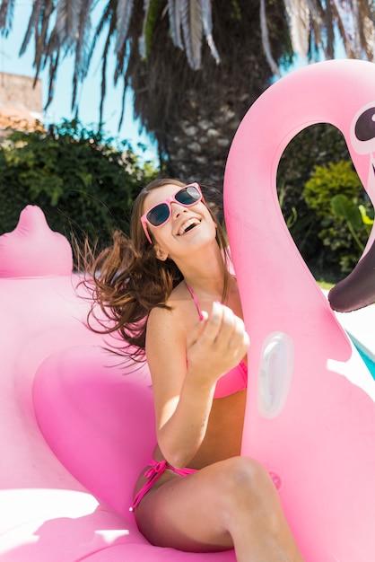 Glückliche frau, die auf aufblasbarem rosa flamingo sitzt Kostenlose Fotos