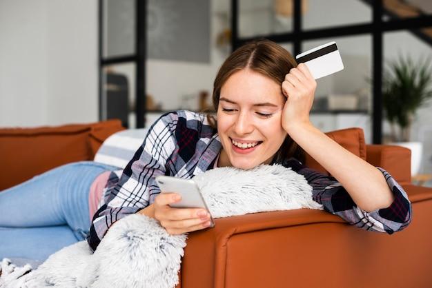 Glückliche frau, die auf dem sofa betrachtet telefon sitzt Kostenlose Fotos