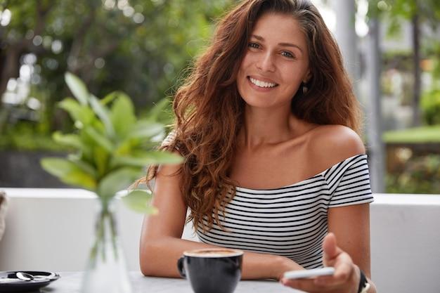Glückliche frau, die auf einem kaffeehaus sitzt Kostenlose Fotos