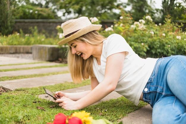 Glückliche frau, die auf gras mit tablette liegt Kostenlose Fotos