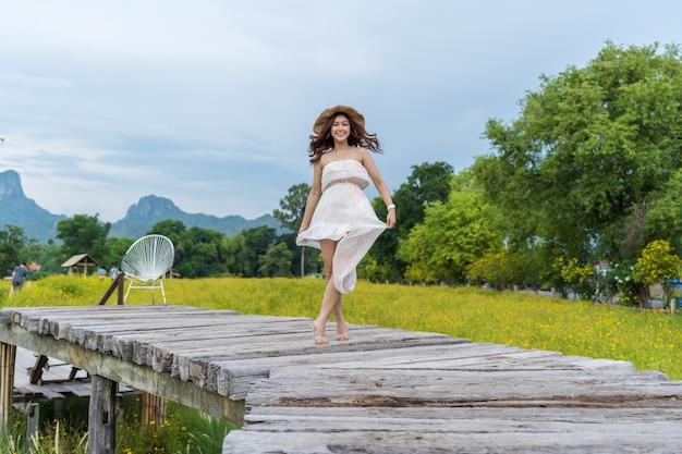 Glückliche frau, die auf holzbrücke mit gelbem kosmosblumenfeld steht Premium Fotos