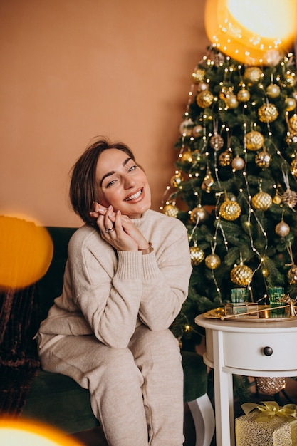 Glückliche frau, die auf sofa durch den weihnachtsbaum sitzt Kostenlose Fotos