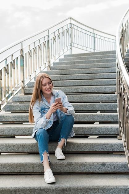 Glückliche frau, die auf treppenhäusern sitzt und smartphone verwendet Kostenlose Fotos