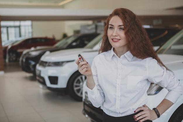 Glückliche frau, die autoschlüssel zu ihrem neuen automobil hält Premium Fotos