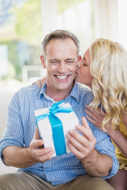 Glückliche frau, die dem ehemann im wohnzimmer geschenk gibt Premium Fotos