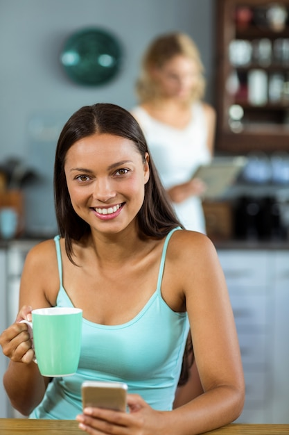 Glückliche frau, die den handy weiß hält, zu hause kaffee trinkend Premium Fotos