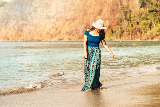 Glückliche frau, die entlang küste schlendert Kostenlose Fotos
