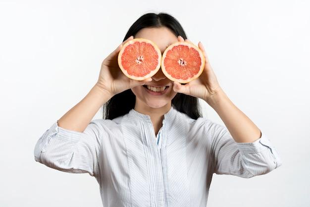 Glückliche frau, die ihre augen mit halbierter traubenfrucht gegen weißen hintergrund bedeckt Kostenlose Fotos