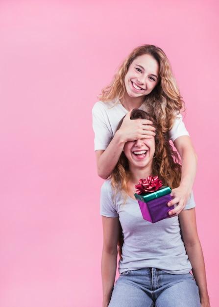 Glückliche frau, die ihrer schwester geschenkbox gegen rosa hintergrund gibt Kostenlose Fotos