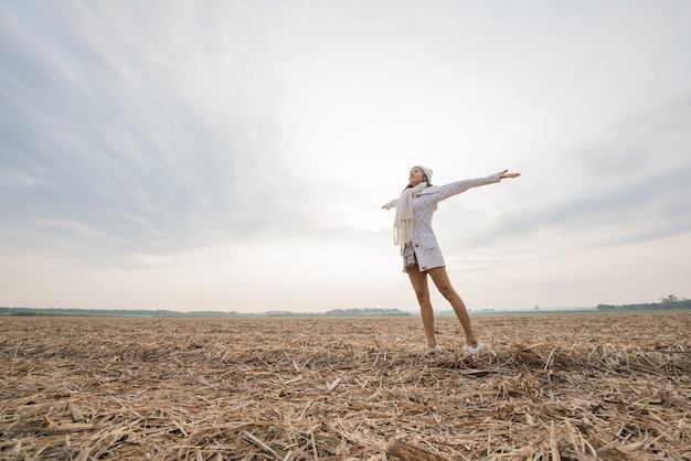 Glückliche frau, die in der idyllischen natur genießt, freiheit feiert und ihre arme steigt Kostenlose Fotos