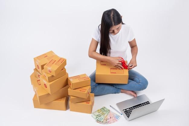 Glückliche frau, die kästen in den on-line-verkäufen verpacken online-arbeitskonzept Kostenlose Fotos