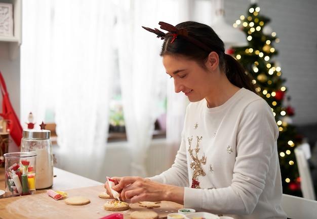 Glückliche frau, die kekse für weihnachten backt Kostenlose Fotos