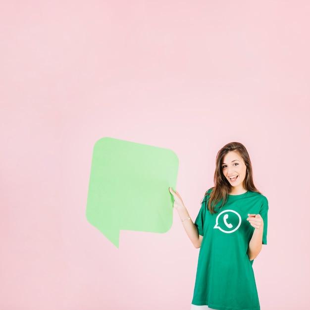 Glückliche frau, die leere grüne spracheblase hält Kostenlose Fotos