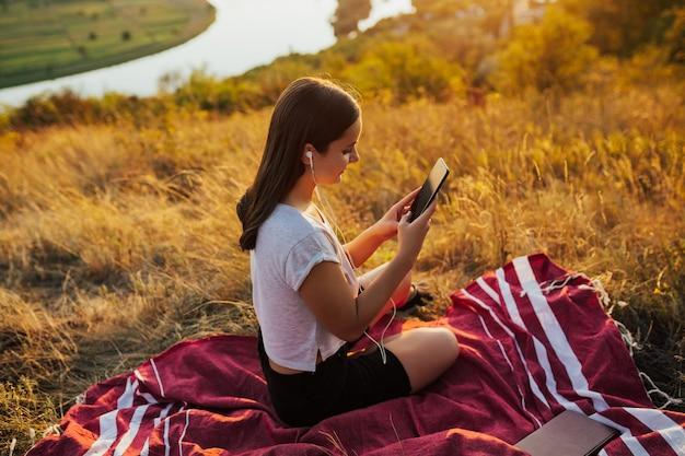 Glückliche frau, die lieblingslieder hört, während sie auf plaid auf dem hügel sitzt. Premium Fotos