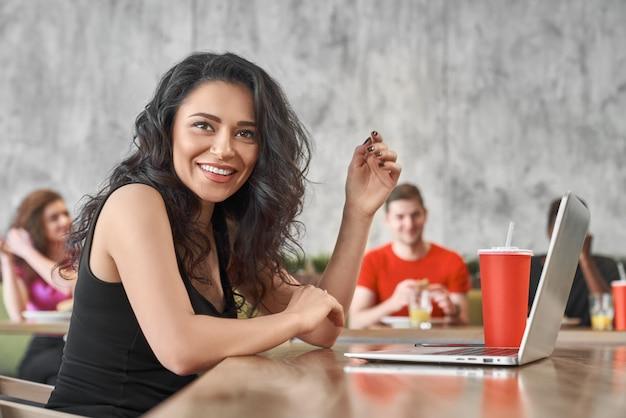 Glückliche frau, die mit computer im café arbeitet und zu mittag isst. junges schönes mädchen, das in internet surft Premium Fotos