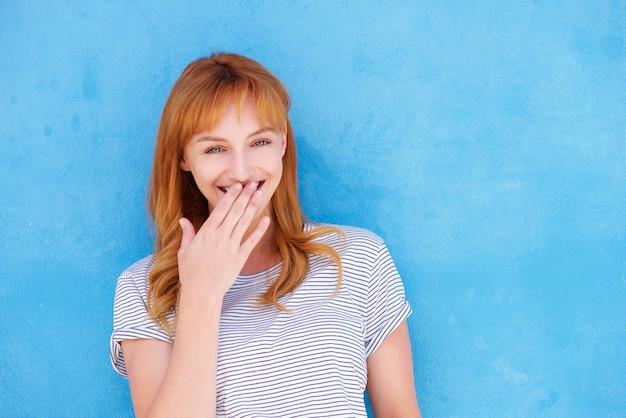 Glückliche frau, die mit der hand lacht, um gegen blaue wand zu mouth Premium Fotos