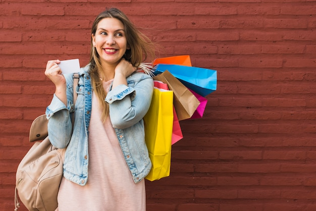 Glückliche frau, die mit einkaufstaschen und kreditkarte an der wand des roten backsteins steht Kostenlose Fotos