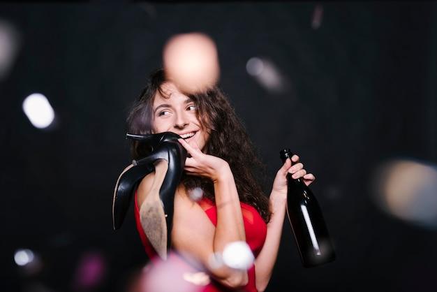 Glückliche frau, die mit flasche auf party steht Kostenlose Fotos