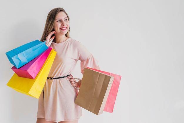 Glückliche frau, die mit hellen einkaufstaschen steht Kostenlose Fotos