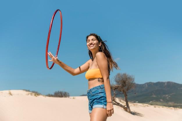 Glückliche frau, die mit hula band auf sand spielt Kostenlose Fotos