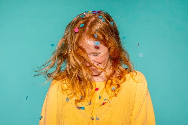 Glückliche frau, die mit konfetti in ihren haaren feiert Kostenlose Fotos