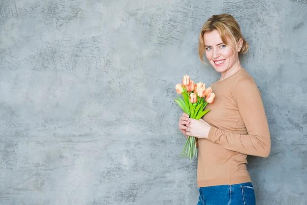 Glückliche frau, die mit tulpenblumenstrauß steht Kostenlose Fotos