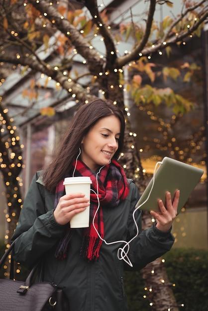 Glückliche frau, die musik auf tablette hört Kostenlose Fotos